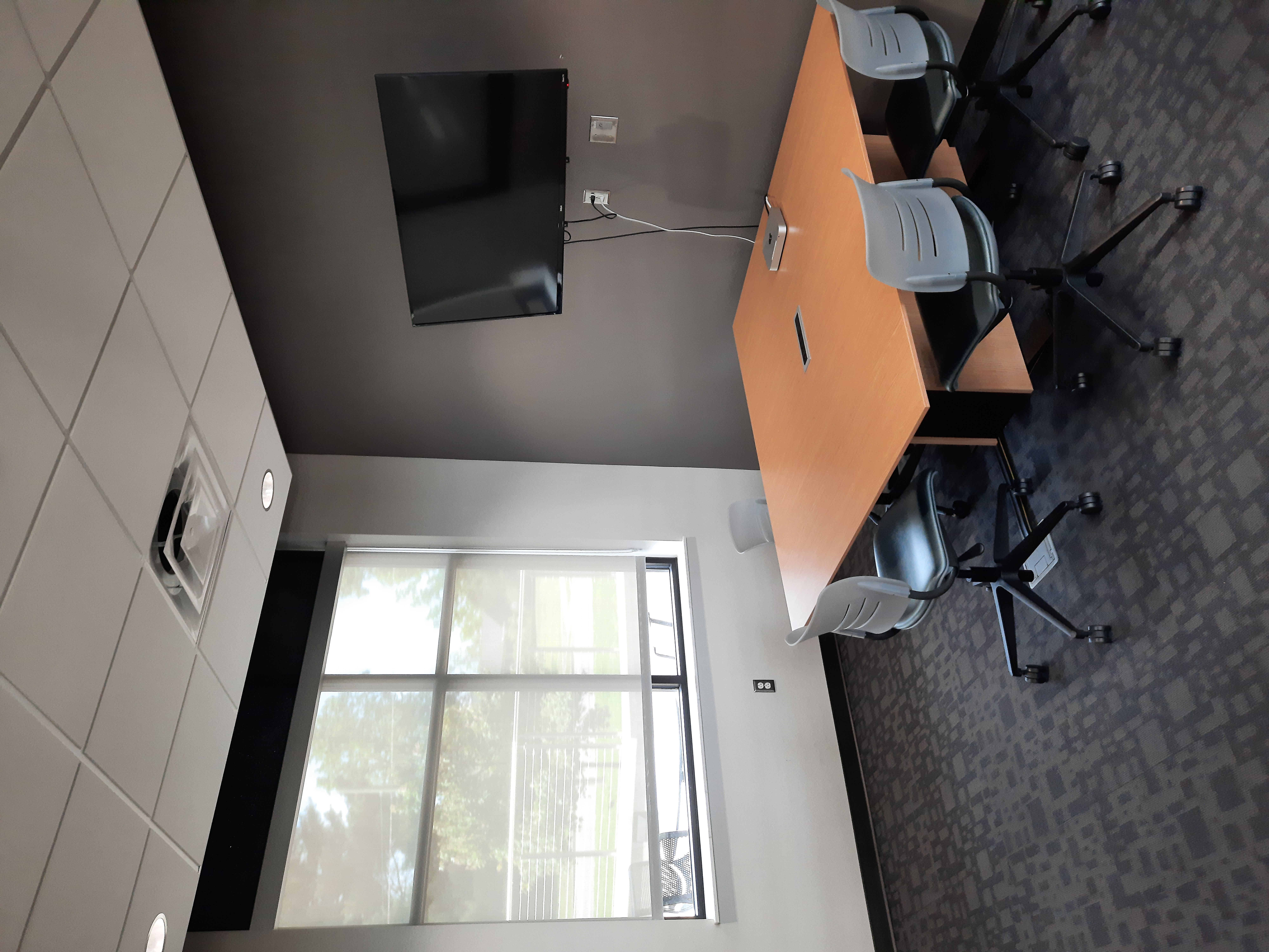 Photo of meeting room with one window. There are six chairs around a table. A tv is on the wall.