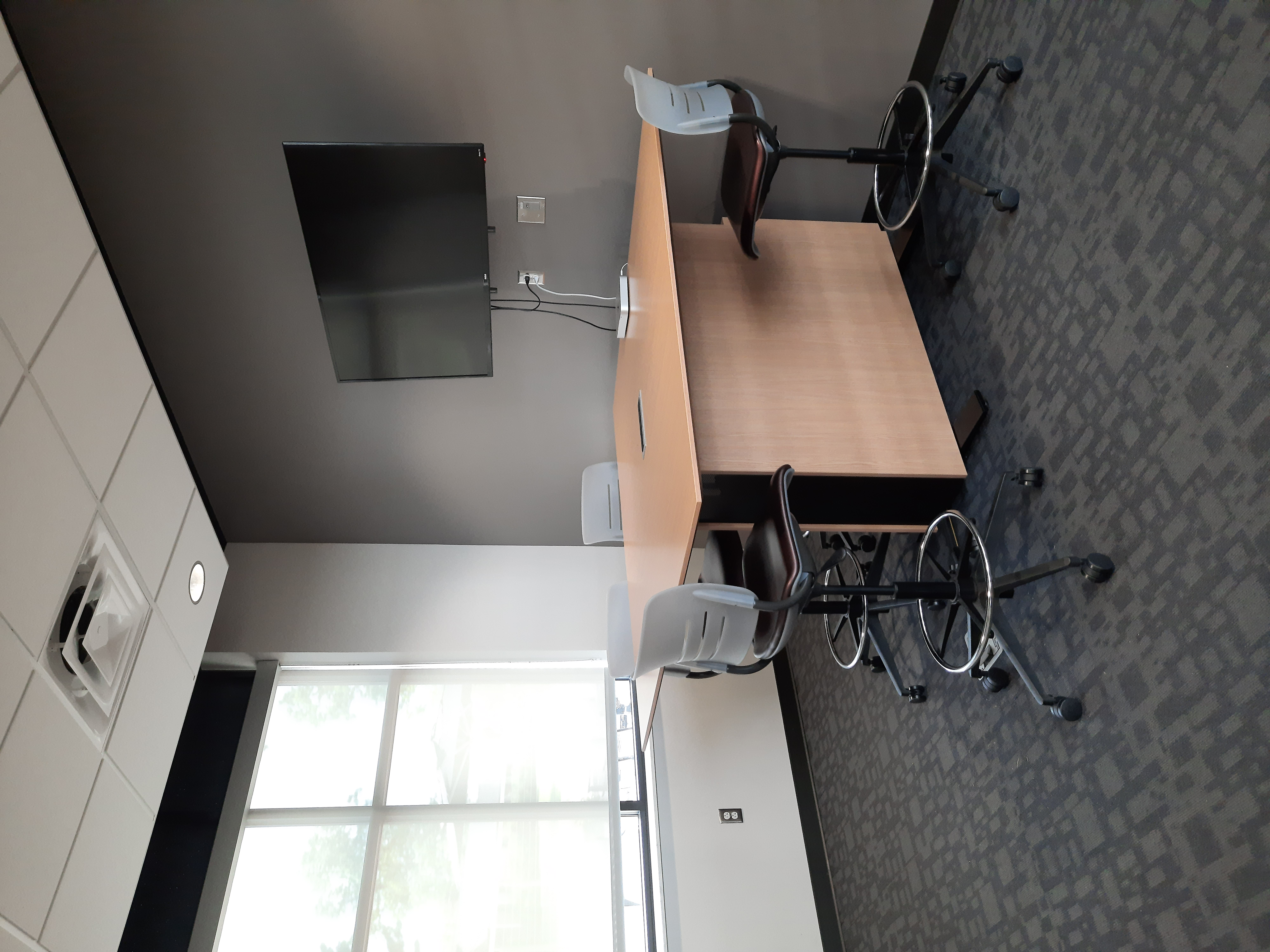 Photo of meeting room with one window. There are six chairs around a high-top table. A tv is on the wall.