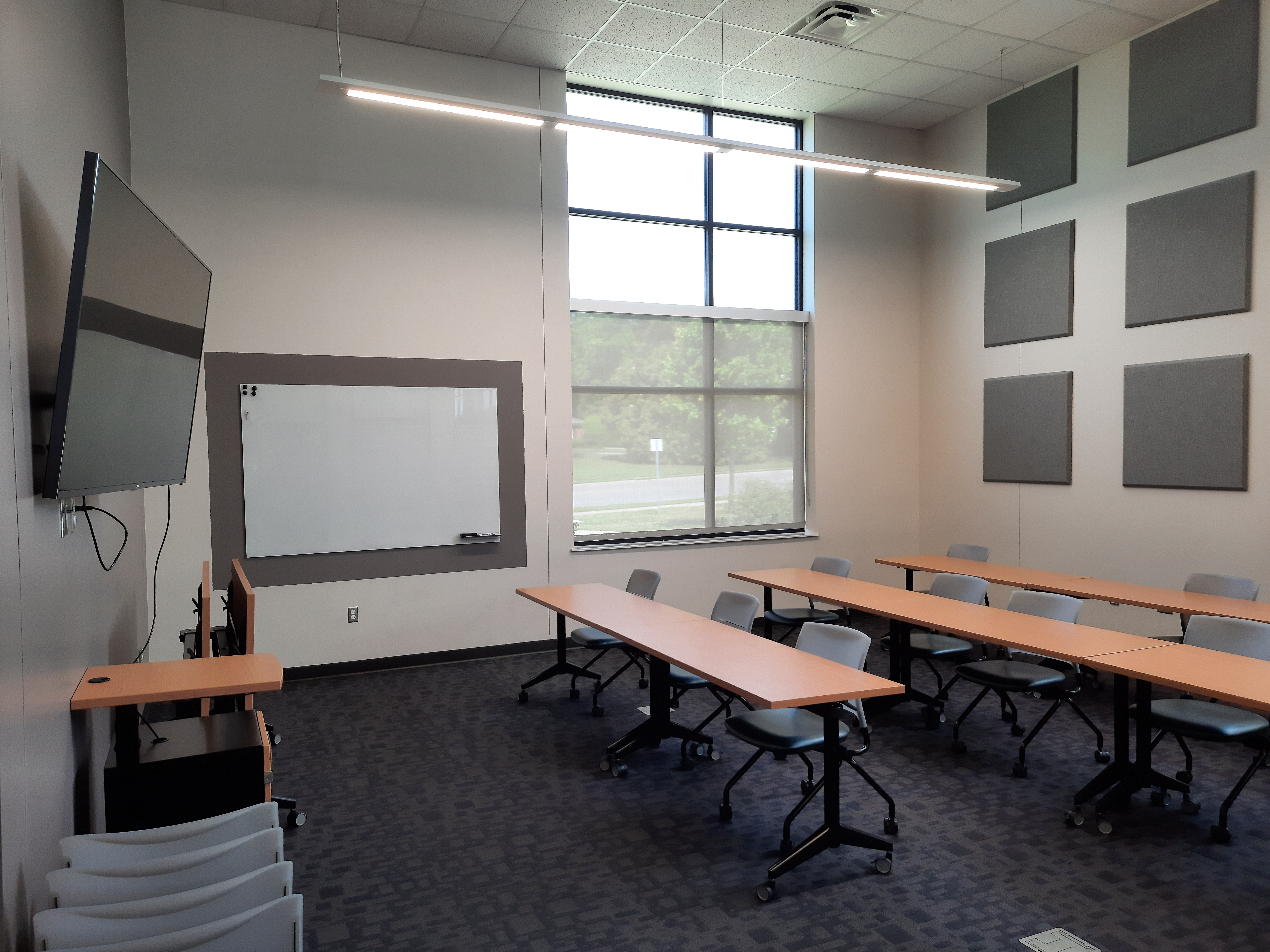 Photo of large meeting room with windows, chairs, and tables. A tv and white board are on the wall.